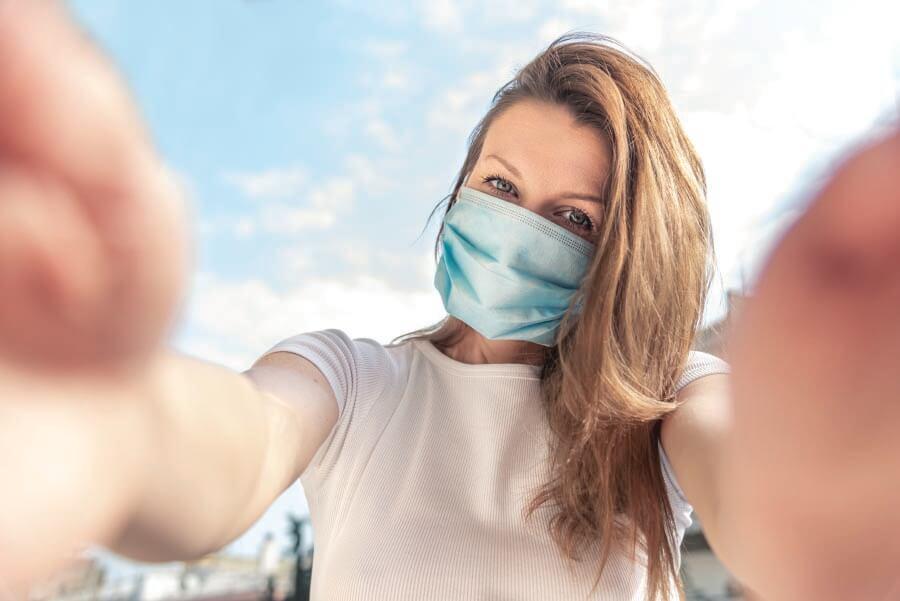 A woman taking a selfie wearing a face mask