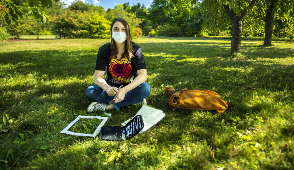 Julia McGuire sitting in grass with lab materials to conduct research