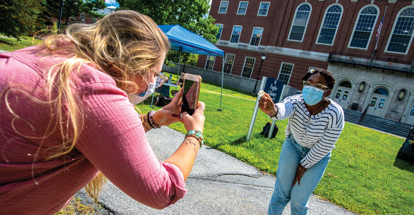A student taking a picture of another student with a smartphone