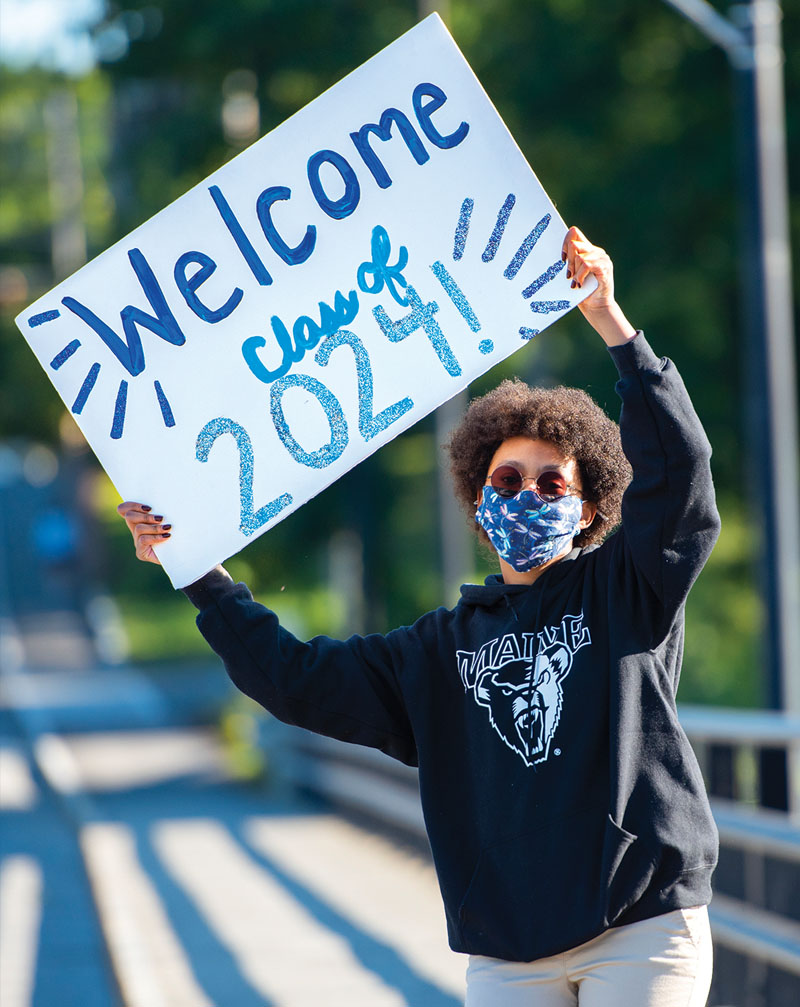 """A woman holds a sign that says, """"Welcome Class of 2024!"""""""