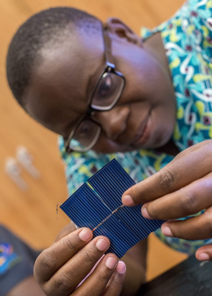 A Mandela Fellow working on a solar panel
