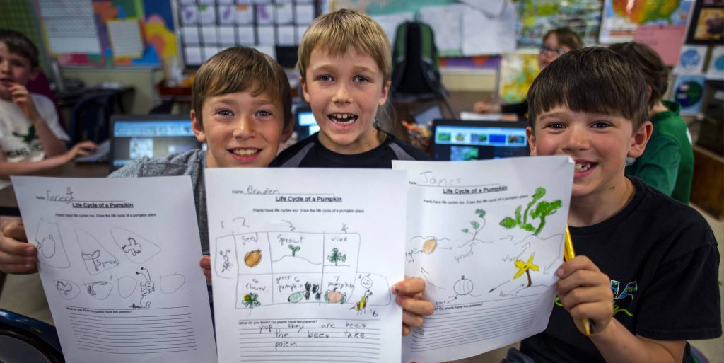 Group of boys showing off a worksheet