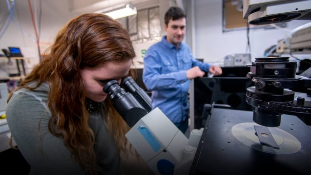 Sam Hess works with his students using a high powered laser microscope to unlock the secrets of the influenza virus with the potential of finding a cure for the illness.